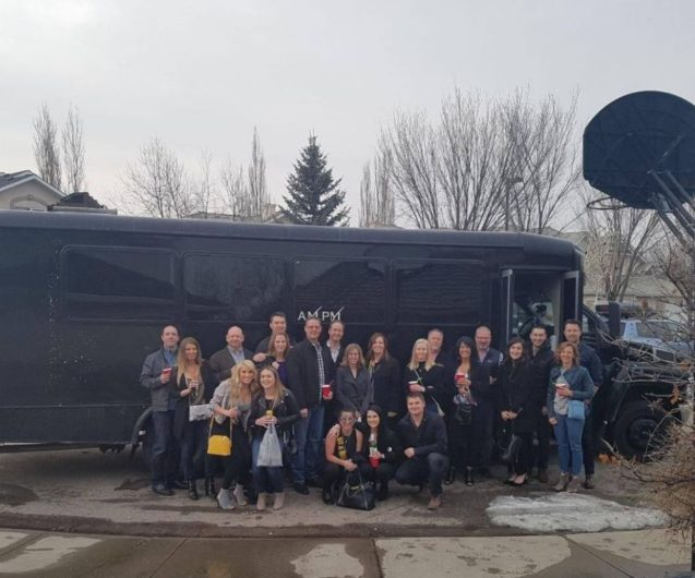 Large group photo in front of a black party bus