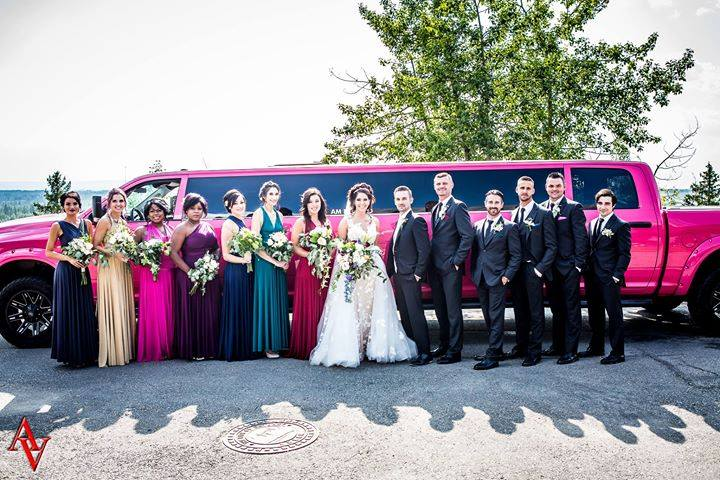 Wedding Party photo in front of Pink Dodge Ram Limo