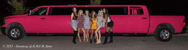 Group of ladies pose for photo in front of Pink Dodge Ram Limousine