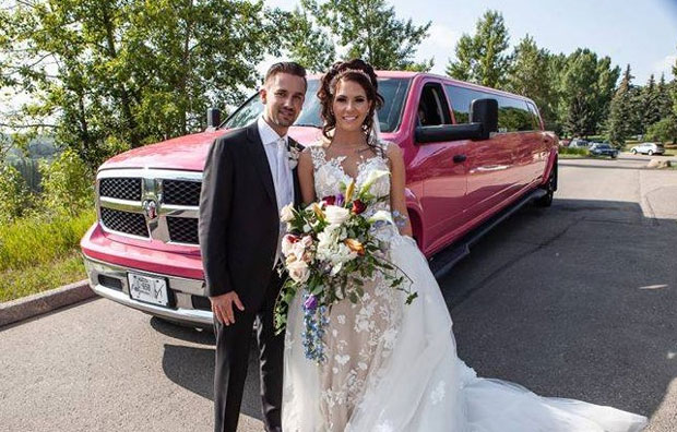 Bride and Groom photo in front of pink Dodge Ram Limousine