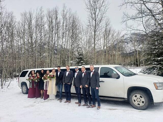 Wedding Party photo in front of the White Suburban Limousine in winter snow in Canmore
