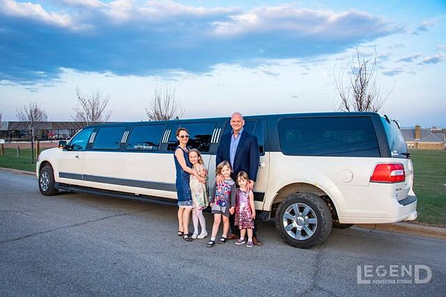 Family photo in front of black and white Lincoln Navigator Limousine
