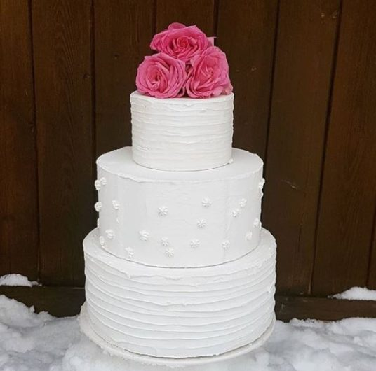 White 3 tier wedding cake with 3 pink flowers on top
