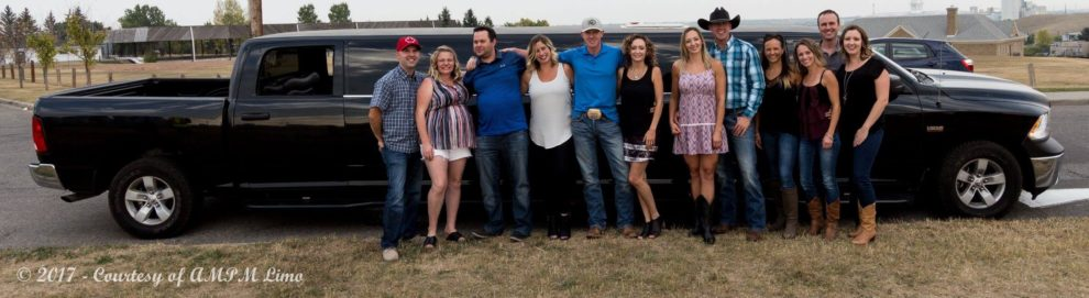 Group photo in front of black Dodge Ram limousine