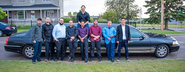 Stag celebration with 9 guys posing for photo in front of a black Lincoln Stretch Limousine