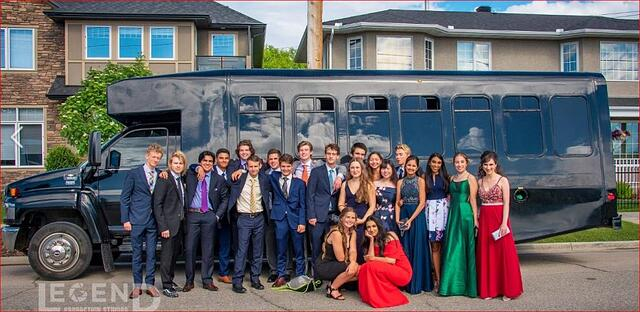 Graduation celebration photo in front of black GMC Party Bus