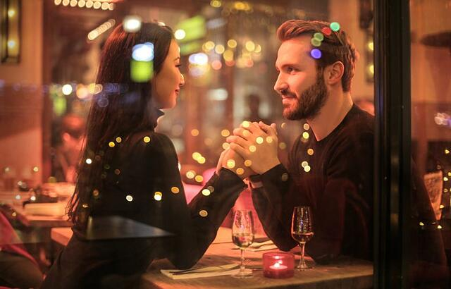 man and women holding hands on a date night setting in restaurant