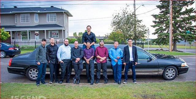 Group of guys standing with black Lincoln Stretch Limousine
