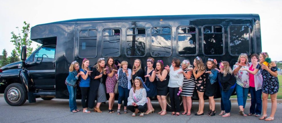 Group of ladies celebrating in front of black party bus