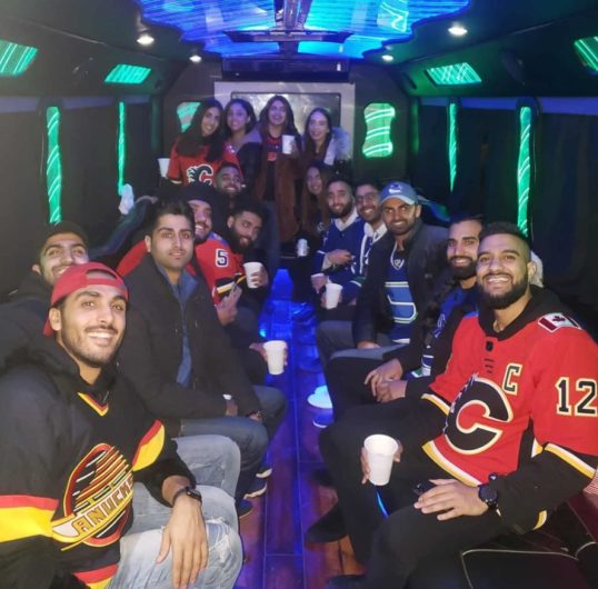 Group photo inside of party bus, everyone is wearing hockey jerseys