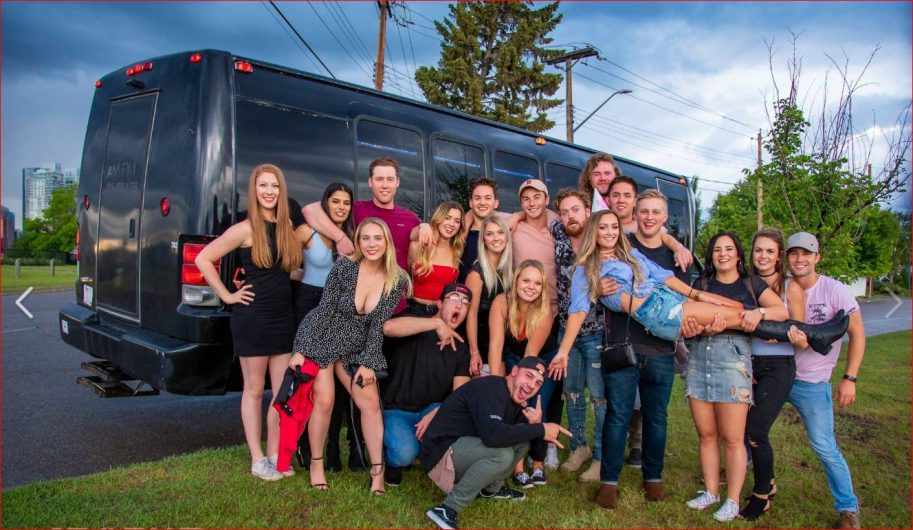 Group celebration photo in front of a black party bus